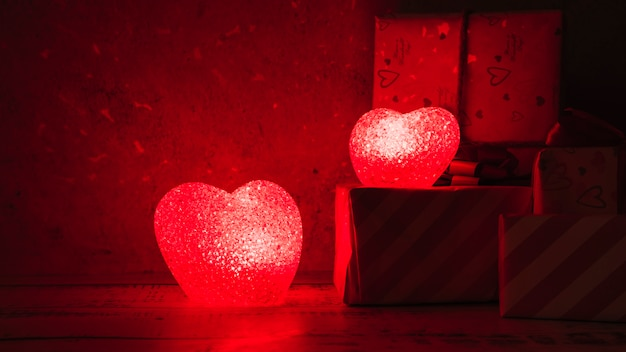 Illuminated lamps in form of hearts near gift boxes