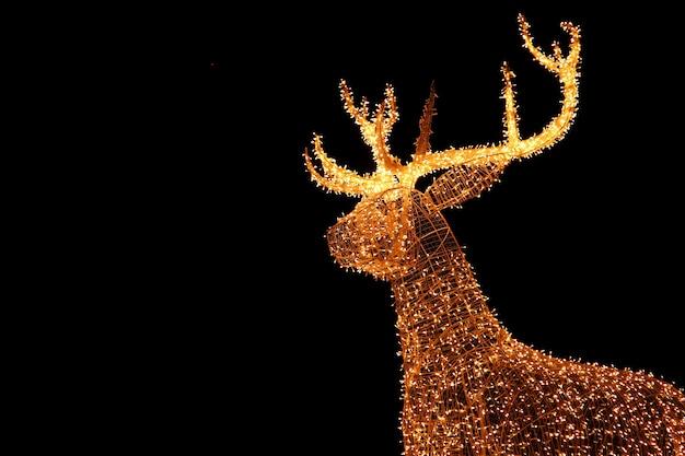 夜空を背景に屋外のクリスマスデコレーションの照らされたledストリングゴールドジャイアントトナカイ