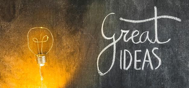 Illuminated light bulb with great ideas text written on chalkboard