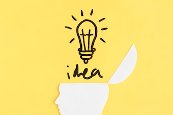 Illuminated light bulb with idea word over open human brain on yellow background