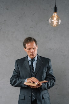 Illuminated lightbulb over the mature businessman reading book against gray wall