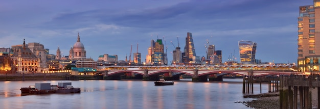 Illuminated london, panoramic view over thames river from waterloo bridge in the evening. this image is toned.