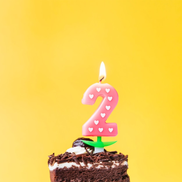 Illuminated love two year candle on cake slice over yellow background