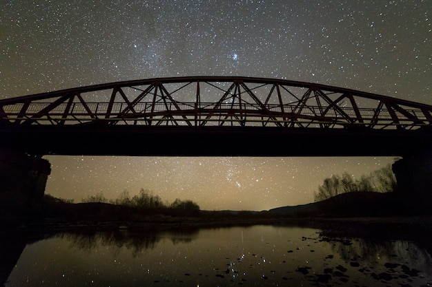 Illuminated metal bridge on concrete supports reflected in water on dark starry sky with milky way constellation background. night photography concept.
