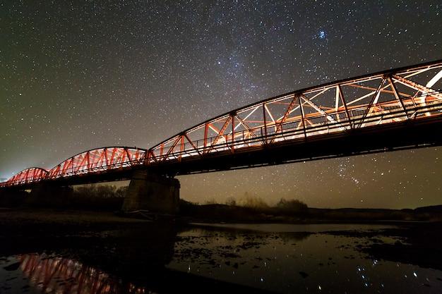 Освещенный металлический мост на бетонных опорах отражается в воде на темном звездном небе с созвездиями млечного пути.