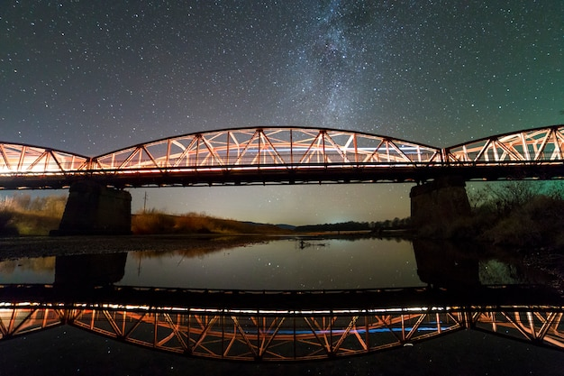 콘크리트 지지대에 조명 된 금속 다리 은하수 별자리와 어두운 별이 빛나는 하늘에 물에 반영. 야간 사진 개념.