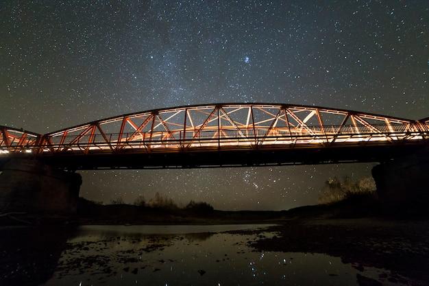 天の川の星座と暗い星空の水に反映されたコンクリート支柱に照らされた金属製の橋。夜の写真のコンセプト。