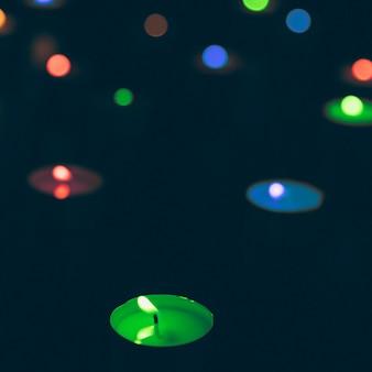 Illuminated multi colored candles on dark background