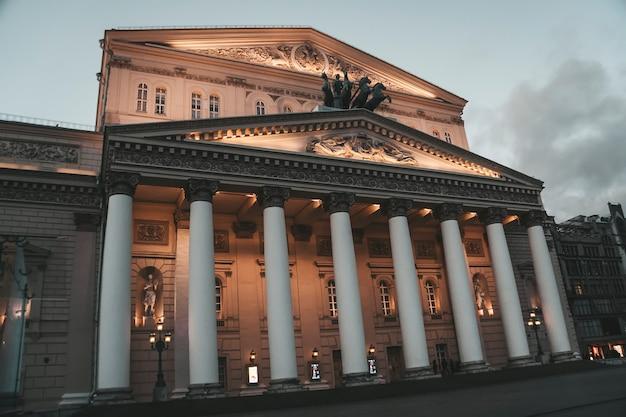 Освещенный неоклассический фасад большого театра на театральной площади в москве, россия. узнаваемые белые колонны и большая скульптурная группа перед зданием русского театра. архитектура