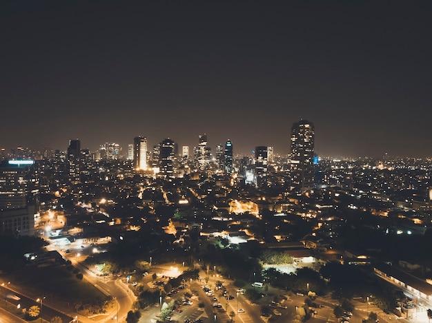 Освещенный ночной город, тель-авив, израиль. ночью сняли жилые кварталы и деловой центр мегаполиса. огни города, городской пейзаж в сумерках. ночная сцена тель-авива, современные здания, темное небо