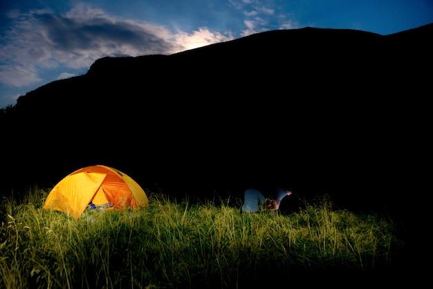 해질녘 들판에 조명이 켜진 주황색 캠핑 텐트