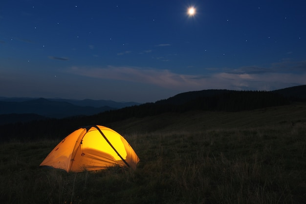 Освещенная оранжевая палатка на вершине горы ночью