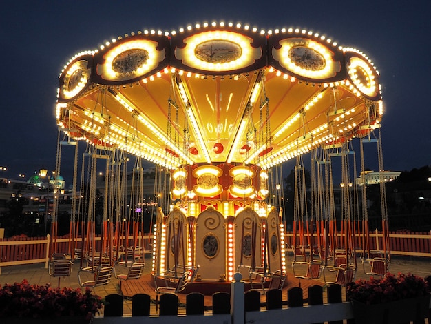 Illuminated retro carousel in the amusement park on the waterfront at night