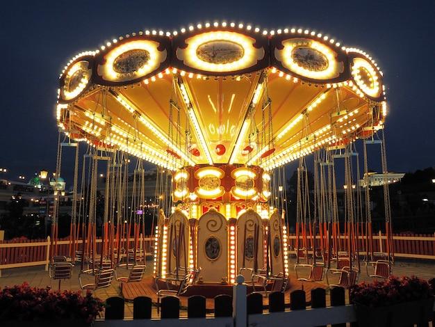 Световая ретро-карусель в парке развлечений на набережной ночью