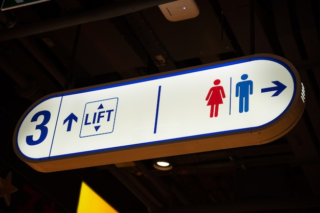 Illuminated signboard level toilet parking lift in shopping mall.