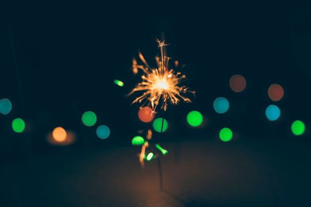 Illuminated sparkler on colorful bokeh background