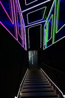 ディスコへの壁と天井の入り口にネオンラインのパターンで飾られた照明付きの階段ダウン