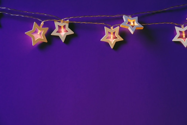 Illuminated star shaped garland on color background close up