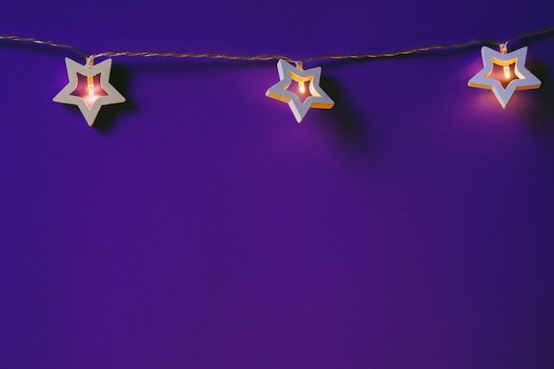 색상 배경에 조명된 별 모양의 화환을 닫습니다.