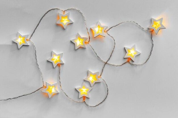 밝은 회색 배경에 조명된 별 모양의 화환
