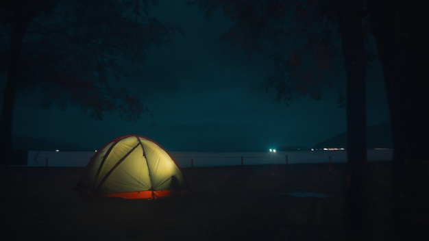 Illuminated tent on the beach under the beautiful mysterious night sky