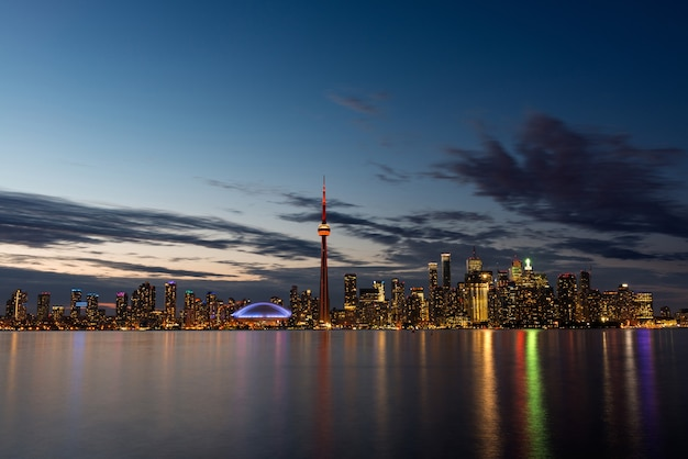 The illuminated toronto skyline with lake ontario in the foreground, as seen from center island.