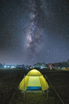 Illuminated tourist tent under beautiful night sky full of stars and milky way