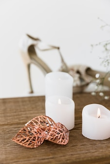 An illuminated white candles on wooden table