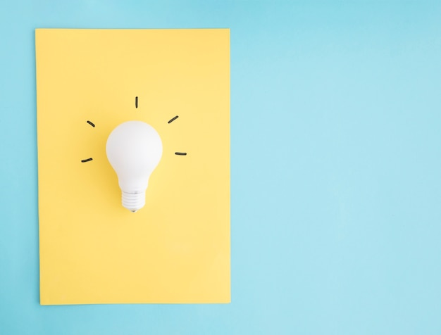 Illuminated white light bulb on yellow paper over the blue background