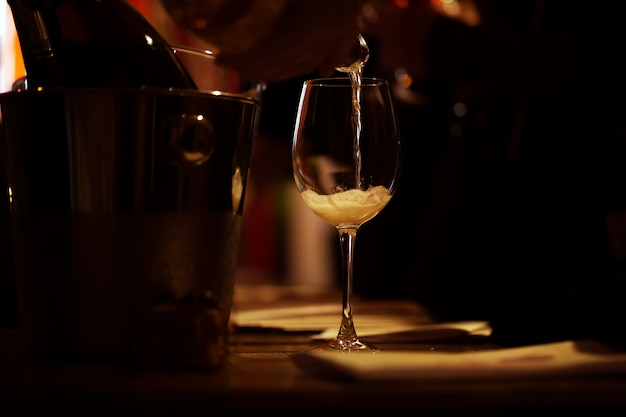 The illuminated wine glass stands on the table and a trickle of pink champagne is poured into it.