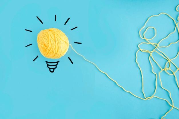 Illuminated yarn yellow light bulb on blue background