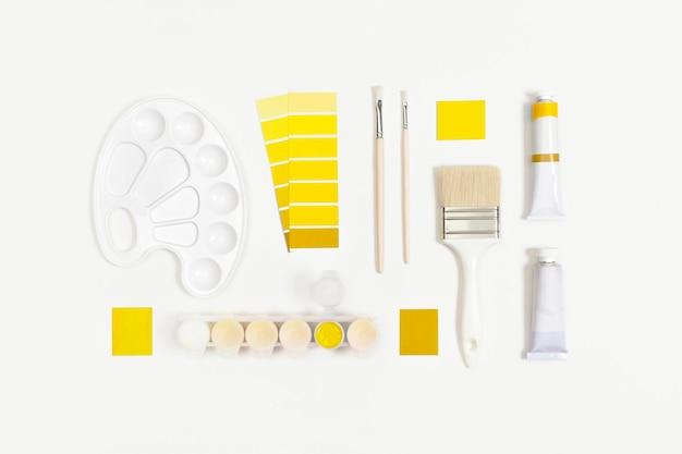Краски illuminating и ultimate grey и белые кисти для рисования. цвета 2021 года. вид сверху, плоская планировка.