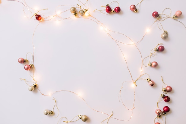 Illuminating fairy lights near christmas baubles