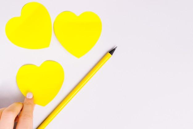 究極の灰色の背景に広告を出すためのハート、鉛筆、空白の形をした照明ステッカー。