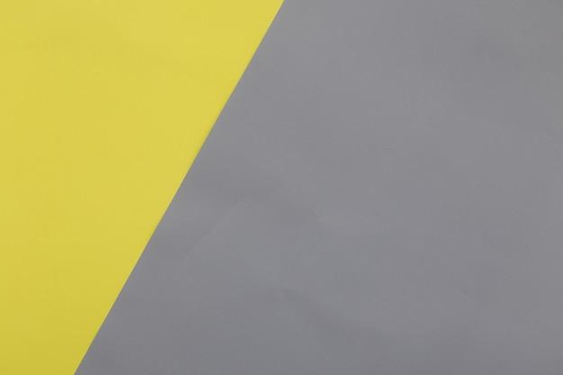 黄色とアルティメットグレーのパステル紙のテクスチャ背景を照らします。