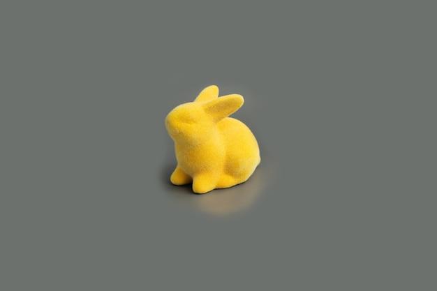 궁극적 인 회색 표면에 노란색 부활절 토끼를 조명. 2021 년 올해의 색상