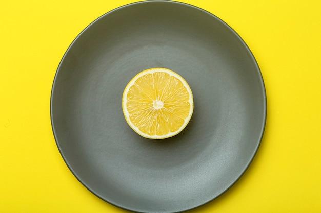 궁극의 회색 접시에 노란색 레몬을 비추고 있습니다. 2021 년 올해의 색상