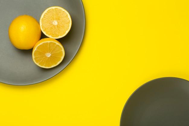 明るい黄色の背景の究極の灰色のプレートに黄色いレモンを照らします。 2021年の色。今年のトレンドカラー
