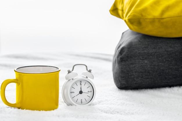 お茶やコーヒーで黄色いマグカップを照らす究極の灰色の目覚まし時計と寝室の年の色の枕