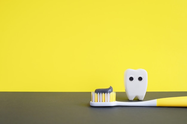 Освещение желтой зубной щетки с зубной пастой и белым игрушечным зубом на сером фоне. концепция стоматологии.