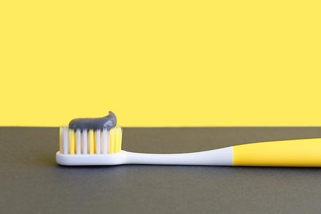 Освещение желтой зубной щетки с зубной пастой на сером фоне. концепция стоматологии. тренд 2021 г.