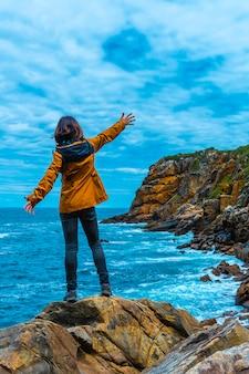 Монте улия в городе сан-себастьян, страна басков. посетите скрытую бухту города под названием illurgita senadia или illurgita senotia. молодая женщина в желтой куртке с распростертыми объятиями, вертикальное фото