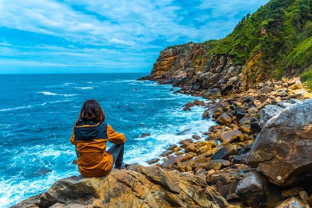 Монте улия в городе сан-себастьян, страна басков. посетите скрытую бухту города под названием illurgita senadia или illurgita senotia. молодая девушка сидит на скалах, глядя на море
