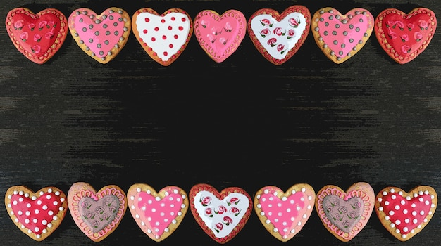 Illustration of frame of beautiful patterned heart shaped royal icing cookies on black background