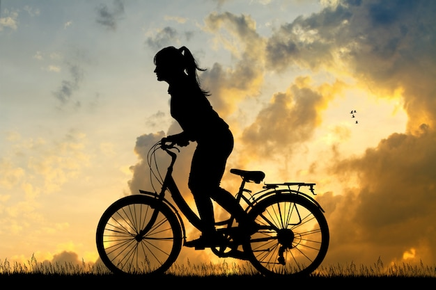 Illustration of girl cycling at sunset