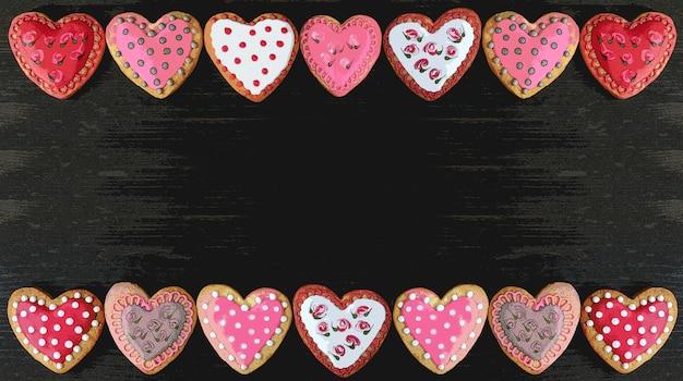 검은 배경에 아름다운 무늬 하트 모양의 왕실 장식 쿠키의 프레임 그림
