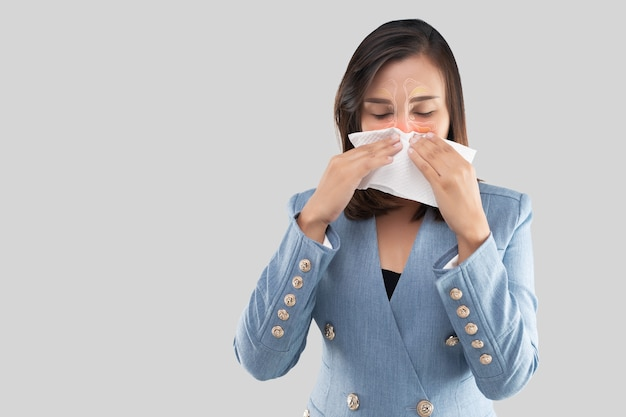 灰色の背景と左側の灰色のスペースに対する女性の顔の鼻腔と副鼻腔のイラスト。女性はティッシュを持って鼻を覆っている。