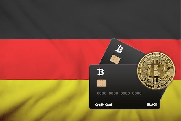 ドイツの旗の背景に2枚の黒いクレジットカードとビットコインコインのイラスト