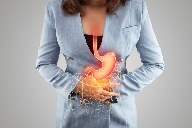 The illustration of stomach and large intestine is on the womans body against gray background