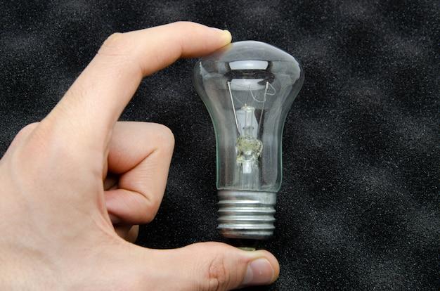 Ilyich bulb, incandescent lamp in men's hands.